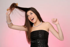Young woman combing her hair. Pink-gray background Stock Image