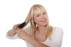 Young woman combing her hair Stock Images