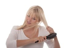 Young woman combing her hair. Young blond woman combing her hair Royalty Free Stock Photos