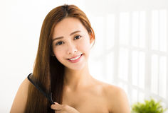 Young  woman combing her hair  in living room Royalty Free Stock Photos
