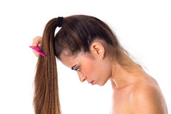 Young woman combing her long ponytail Royalty Free Stock Photography