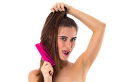 Young woman combing her long ponytail Stock Photo