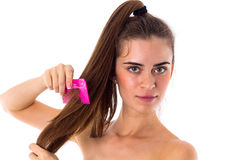 Young woman combing her long ponytail Stock Photography