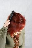 The young woman combs hair. The beautiful woman combs the hair Royalty Free Stock Photo
