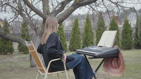 Young woman comes and sits at keyboard instrument outdoors, preparing to play. Notebook with notes is on a stand in. Front of the girl. Female musician in stock video footage