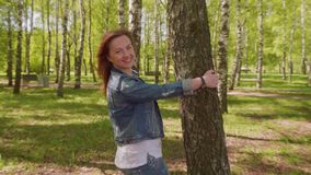 Young woman comes up to tree puts hand on it, turns around her head and smiles looking at camera stock video footage