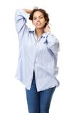 Young woman in comfortable shirt and jeans smiling with hands in hair Royalty Free Stock Images