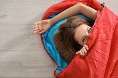 Young woman in comfortable sleeping bag on floor stock images