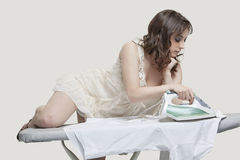 Young woman comfortably ironing shirt against gray background Royalty Free Stock Photo