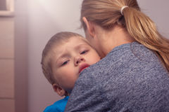 Young woman comforting her little son. Young women comforting her little son. Mother and child hugging Stock Photos
