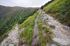 Young woman coming down on mountain trail Royalty Free Stock Photo