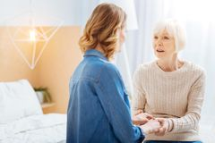 Young woman coming to her grandmother and touching her hands while talking. Urgent talk. Emotional senior lady sitting on a soft bed in front of her kind young Royalty Free Stock Photo