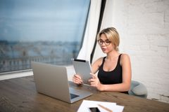 Female secretary big successful company using digital tablet and net-book. Young woman commercial real estate analyst reading e-mail on touch pad, sitting at the Royalty Free Stock Images