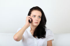 Young woman communicates via her cell phone with upset expression Stock Photography