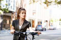 Young woman commuting on bicycle Stock Photos