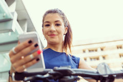 Young woman commuting on bicycle holding a mobile Stock Photos