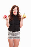 Young woman comparing an apple and a pear, trying to decide whic Stock Photos
