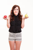 Young woman comparing an apple and a pear, trying to decide whic Stock Image