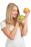 Young woman comparing apple to orange Stock Photo