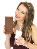 Young Woman Comparing a Chocolate Bar to a Glass of Sugar Stock Photography