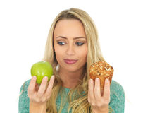 Young Woman Comparing Good and Bad Food. A DSLR royalty free image, of an attractive young woman with blonde hair, comparing good and bad between an apple and royalty free stock image