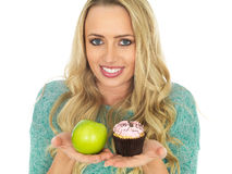 Young Woman Comparing Good and Bad Food. A DSLR royalty free image, of attractive young health conscious young woman smiling, with long blonde wavy hair, holding royalty free stock image
