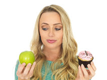 Young Woman Comparing Good and Bad Food. Young Woman Holding and Comparing Cake and Fruit royalty free stock photo