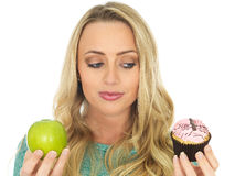 Young Woman Comparing Good and Bad Food. Young Woman Holding and Comparing Cake and Fruit royalty free stock image