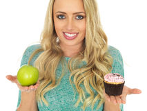 Young Woman Comparing Good and Bad Food Royalty Free Stock Photos