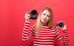 Young woman comparing professional and compact cameras. On a solid background Stock Photo