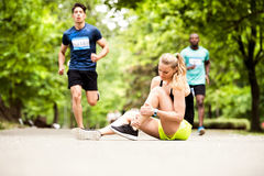 Young woman at the competition with sprained ankle. Stock Image