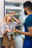 Young woman complaining to black handyman on problems. Upset young women complaining to black handyman on problems with fridge Royalty Free Stock Photo