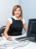 Young woman at computer. A young caucasian woman sitting in front of a computer looks into camera and smiles Stock Photo