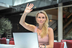 Young woman computer. An attractive young woman with a laptop raising her hand and smile Royalty Free Stock Photos