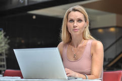 Young woman computer. An attractive young woman with a computer in a public Place smiling Royalty Free Stock Images