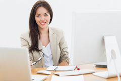Young woman with computers at desk in office Royalty Free Stock Photos