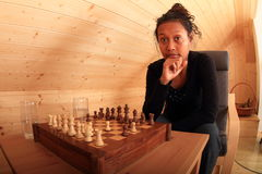 Young woman concentrated for next move in chess. Young Papuan woman - girl sitting on armchair and concentrating for next move in chess in wooden attic room stock image