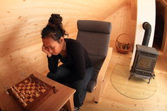 Young woman concentrated for next move in chess. Young Papuan woman - girl sitting on armchair and concentrating for next move in chess in wooden attic room with royalty free stock images