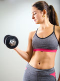 Young woman concentrating on dumbbell curl. Photo of an attractive woman doing a dumbbell curl while standing Stock Images