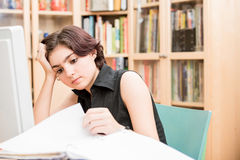 Young Woman Concentrating. Teenager or young woman concentrating with books and a computer in front of a bookshelf stock photography