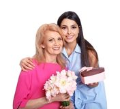 Young woman congratulating her mature mom on white. Happy Mother`s Day stock photos