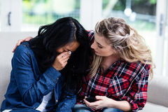 Young woman consoling crying female friend at home Stock Image