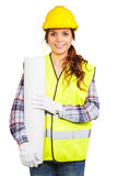 Young woman in construction helmet and yellow vest. Girl worker in a construction helmet and yellow vest holds blueprint, isolated Stock Image