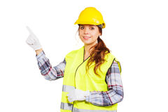 Young woman in construction helmet and yellow vest. Girl worker in a construction helmet and yellow vest shows index finger upward, isolated Royalty Free Stock Photo