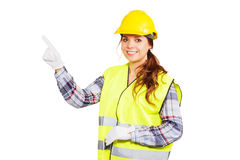 Young woman in construction helmet and yellow vest. Girl worker in a construction helmet and yellow vest shows index finger upward, isolated Stock Photography