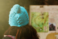 Young woman consulting a map information board, hiking trails in Stock Photography