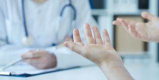 Young woman consulting with medical doctorcomplaining about health, having problems. Focus on patient`s hands. Private stock images