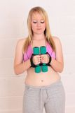 Young woman contemplating her exercise weights Stock Images