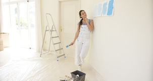 Young woman contemplating new paint for her home Royalty Free Stock Images