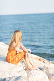 Young woman contemplating the ocean Stock Images